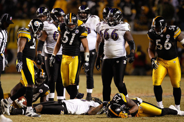 PITTSBURGH - JANUARY 18: Teammates look on as Ryan Clark #25 of the Pittsburgh Steelers lie on the field Willis McGahee #23 the Baltimore Ravens after Clark laid a hard hit on McGahee during the AFC Championship game on January 18, 2009 at Heinz Field in Pittsburgh, Pennsylvania. McGahee was taken off the field on a backboard by medical personnel (Photo by Streeter Lecka/Getty Images)